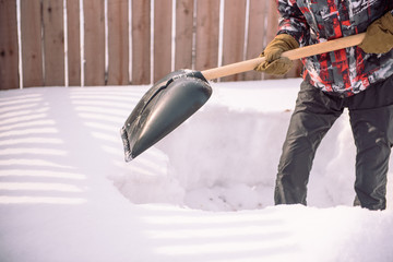 Clean the snow with a shovel. The man shovels snow shovels. Snow shovel in hand. Cleaning the area in the winter.