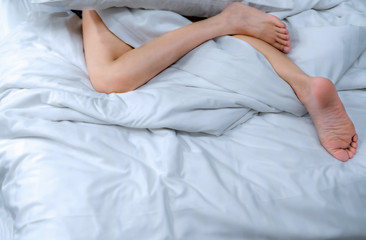 Poster Spa Close up woman bare feet on the bed over white blanket and bed sheet in the bedroom of home or hotel. Sleeping and relax concept. Lazy morning. Barefoot of woman lying on white comfort bed and duvet.