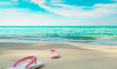 Pink and white sandals on sand beach. Casual style flip-flop were removed at seaside. Summer vacation on tropical beach. Fun holiday travel on sandy beach. Summertime. Summer vibes. Relaxing time.