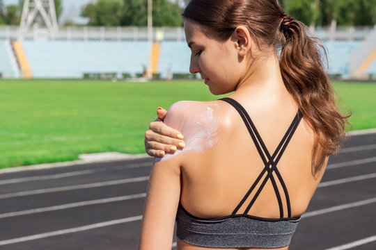 Sunscreen sunblock. Woman in a sportswear putting solar cream on shoulder on beautiful summer day. Sporty woman applying sunscreen on sport stadium. Sports and healthy concept