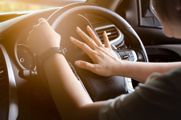 Closeup hands of asian woman,hand pushing on steering wheel honking horn, on the road,female driver concept