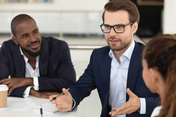 Millennial boss leading corporate multiracial team meeting at boardroom