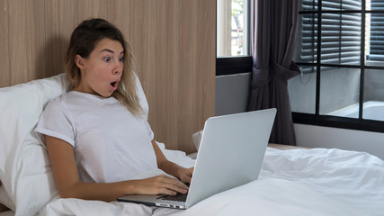 attractive young model in sleepwear posing with laptop at home in the bedroom,