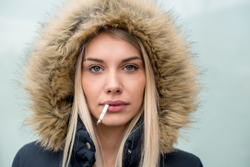 portrait of young blonde girl with cigarette in the mouth