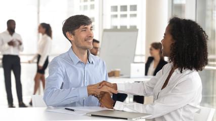 Caucasian male handshaking african female satisfied by good work result