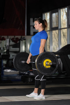 Young woman doing deadlift workout with heavy barbell in dark gym