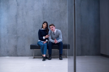 business couple using mobile phone while sitting on the bench