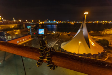 Action camera on tripod that takes over the port of Bari at night from the balustrade of a ship, Italy