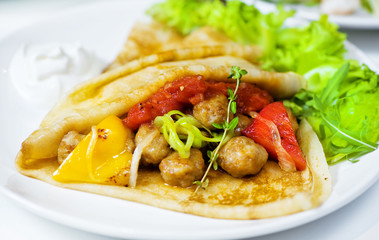 Thin delicious pancake with meat balls and pepper on white