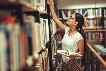 Young female student read and learns by the book shelf at the library.