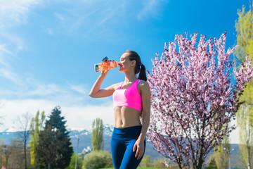 Woman having break from running drinking water