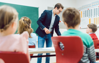 Teacher handing back written tests to the class