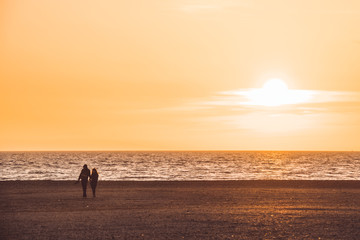silhouette of couple walking on the beach on orange sunset background, almerimar, almeria, spain