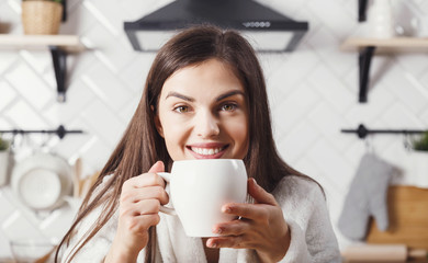 Brunette woman smiling at the kitchen with white cup