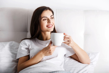 Happy young woman with cup of coffee or tea in bed at home bedroom