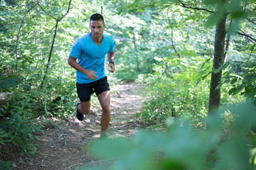 Young man running in the woods forest