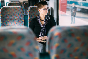 Alternative young woman reading a book on train