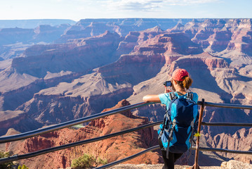 Young woman standing on the edge of Grand Canyon taking a photograph. Grand Canyon hiker woman resting. Hiking caucasian girl relaxing on  South rim of Grand Canyon, Arizona. Wall mural