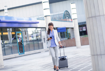 Young woman on business trip walking with her luggage at airport.