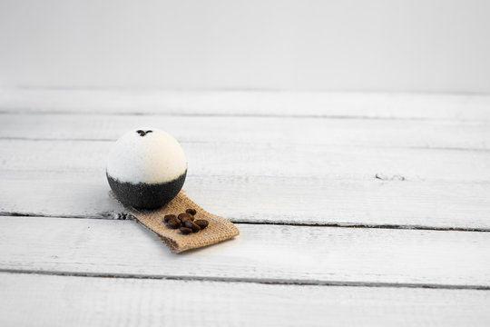 Bath bombs with coffee grains on a wood background