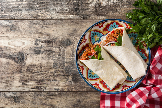 Typical Mexican burrito wrap with beef, frijoles and vegetables on wooden table. Top view. Copyspace