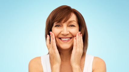 beauty, skin care and old people concept - portrait of smiling senior woman touching her face over blue background