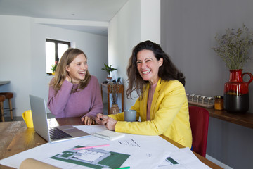 Female architects working with drawings and laughing