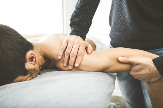 Chiropractor massaging a young man shoulder. Concept of physiotherapy