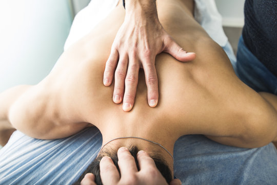 Physiotherapist massaging the back and neck of a young man. Concept of wellness and physiotherapy