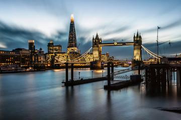Die beleuchtete Skyline von London, Großbritannien, am Abend mit Themse, Tower Bridge und modernen Hochhäusern