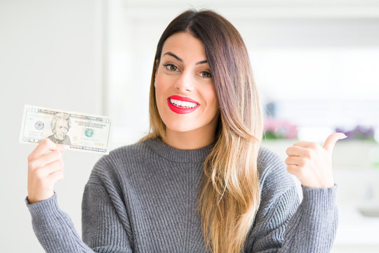 Young beautiful woman holding 20 dollars bank note at home pointing and showing with thumb up to the side with happy face smiling