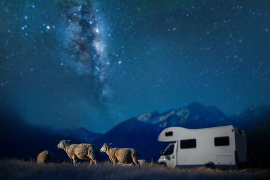 Sheeps and blur Motor Home or Campervan or Home car on the hill and  Blur Milky Way Background  in New zealand lacations
