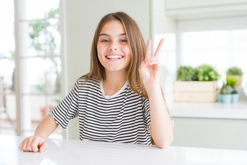Beautiful young girl kid wearing stripes t-shirt showing and pointing up with fingers number two while smiling confident and happy.