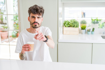 Young man drinking a coffee in a paper cup in the morning pointing with finger to the camera and to you, hand sign, positive and confident gesture from the front