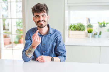 Young man wearing casual shirt sitting on white table Beckoning come here gesture with hand inviting happy and smiling