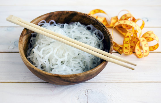 Chinese dietary noodles shirataki konjak in a wooden bowl with chinese chopsticks. Near the tape to measure the body. Gluten-free diet for weight loss.