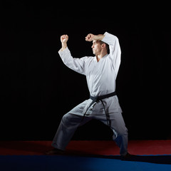 On the red and blue tatami athlete doing formal karate exercises