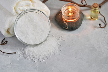 Close up view of Spa relax concept. White Terry towels, stones, candle, sea salt on a gray textured background.