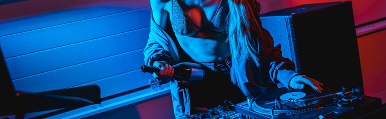 panoramic shot of dj woman holding bottle while touching vinyl record