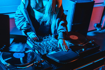 cropped view of dj woman touching dj mixer in nightclub