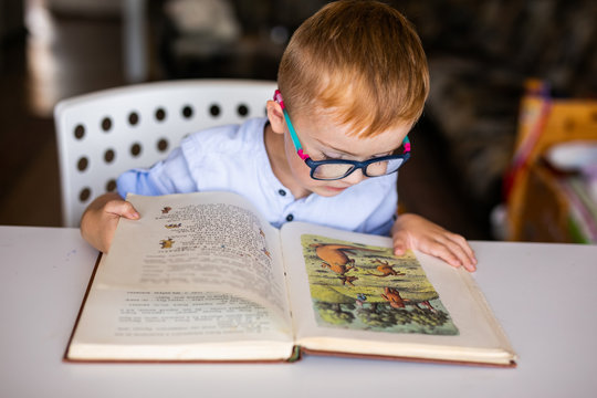 cute boy, kid with special needs looking at a book, in rehabilitation center