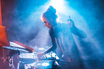 concentrated dj woman with blonde hair gesturing and using dj equipment in nightclub with smoke Wall mural