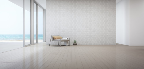 Wall Mural - Sea view living room of luxury beach house with armchair near door on wooden floor. Empty white triangle pattern wall background in vacation home or holiday villa. Hotel interior 3d illustration.