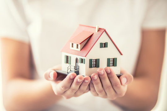 Hands of young woman holding model house