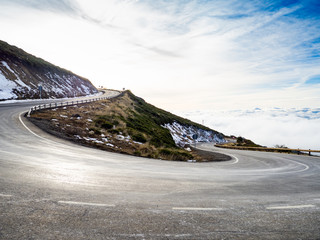 Very closed curve on a dangerous high mountain road with cloudy skies and snow on La Covatilla, Bejar (Salamanca)