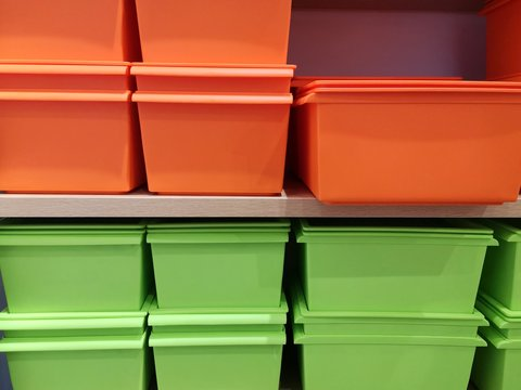 Stack of new bright empty plastic container. Set of orange and green containers for food or cloth. Kitchen  organization box