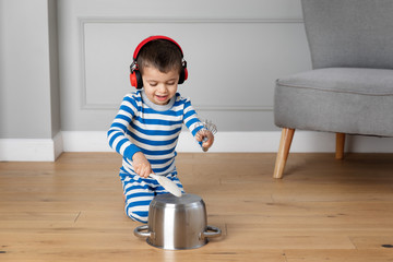Young child wearing headphones playing drums with pots and pans