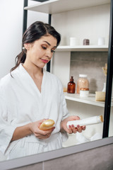 woman in white bathrobe looking to mirror and holding bottles with shower gel in bathroom