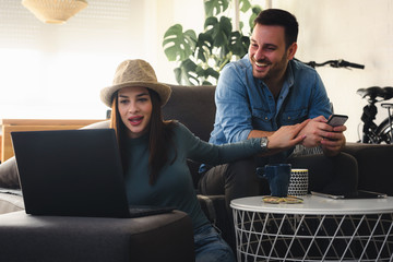 Young couple shopping online, lying on sofa and looking at laptop at home. Girl is very excited.