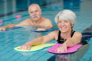 happy senior couple taking swimming lessons